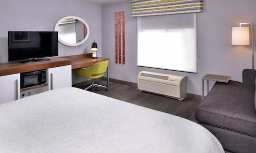 Bed in room with workdesk and TV