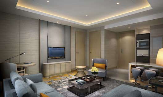 Guestroom Lounge Area with L-Shaped Sofa, Armchair and Wall Mounted HDTV