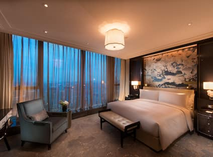 Executive suite with king bed, footrest, soft chair, TV, and large art displayed above bed