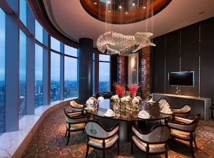 Chinese restaurant private dining room with large dining table, chairs, dining amenities, TV, and floor-to-ceiling windows with city view