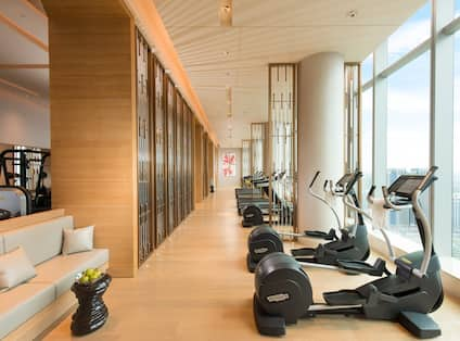 Fitness center with long row of treadmills and ellipticals, facing floor-to-ceiling windows with outdoor view