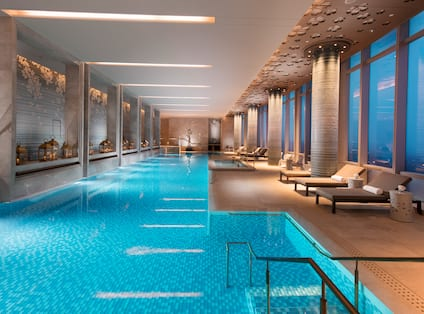 Lavish indoor pool with lounge chairs and floor-to-ceiling windows with outdoor view, lit up at night