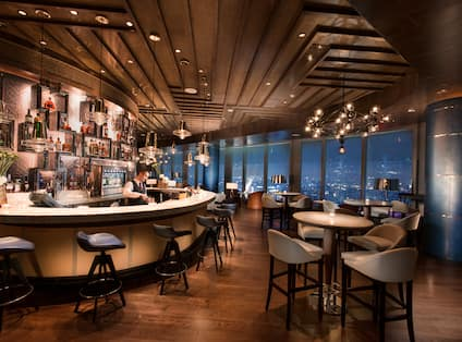Sip Wine bar with high-top tables, chairs, and windows with outdoor view, lit up at night