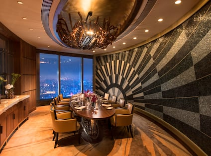 The Grill restaurant private dining room with large dining table, chairs, dining amenities, and floor-to-ceiling window with city view at night