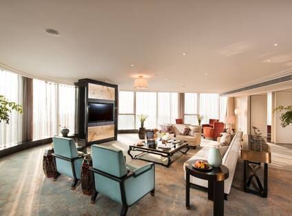 Presidential Suite Lounge Area with Wall Mounted HDTV, Coffee Table, Armchairs and Sofas