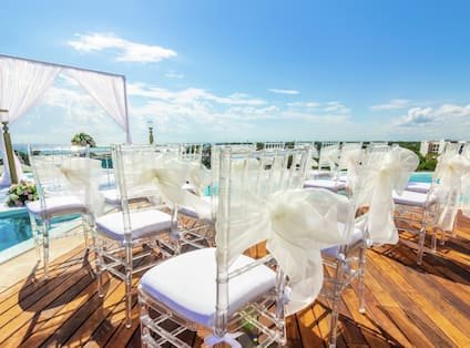 Chairs, Decorations, and Wedding Arch Set Up on Rooftop for Wedding