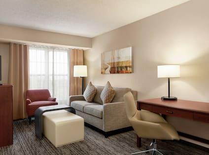Lounge Area, TV, and Work Desk in One Queen Bedroom Suite