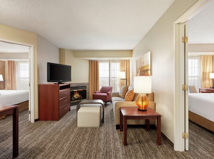 Lounge Area, Fireplace, and TV in Two Queen Bedroom Suite