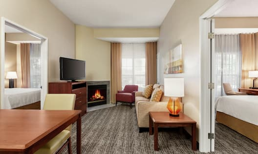 Accessible Suite Living Area with Lounge Furniture, Fireplace, TV, and Dining Table