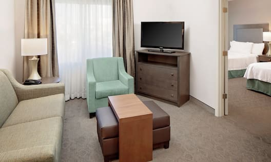 Guestroom seating area with couch, chair and TV