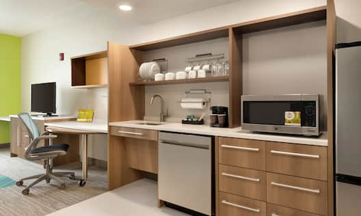 Spacious living area in accessible suite featuring fully equipped kitchen, work desk, and TV.