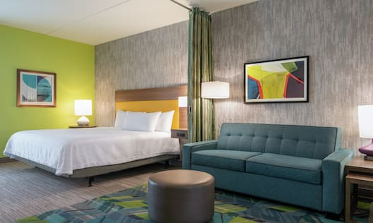 Spacious accessible suite featuring sofa, privacy curtain, and comfortable queen bed.