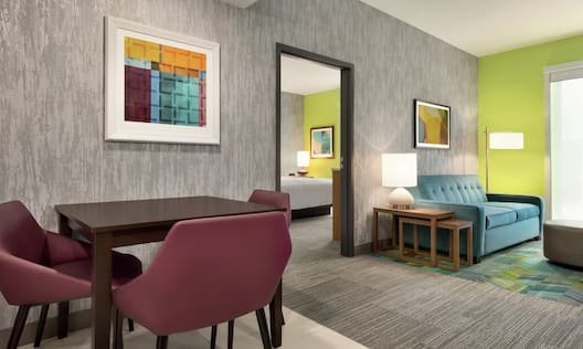 Spacious living area in suite featuring dining table, sofa, and private bedroom with comfortable king bed.