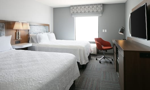 Guest Room with Two Beds Desk and HDTV