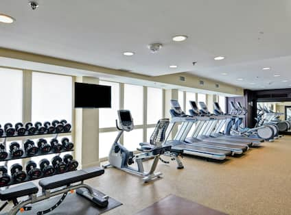 Fitness Center with Treadmills, Dumbbells, Elliptical Machines, Mirror, and Room Technology