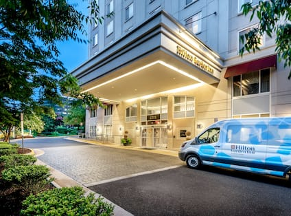 Hotel Building Exterior Front Entrance with Shuttle Van at Dusk