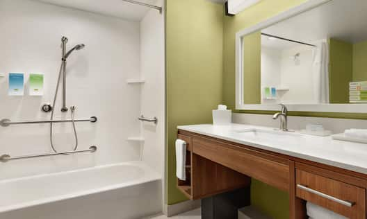 Spacious accessible bathroom featuring tub, mobile shower head, vanity, and mirror.