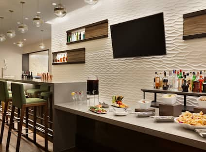 Bar Lounge Area with Bar Counter, Bar Stools and Wall Mounted HDTV