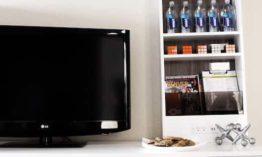 a tv and plate of cookies on a counter and a shelf with amenities