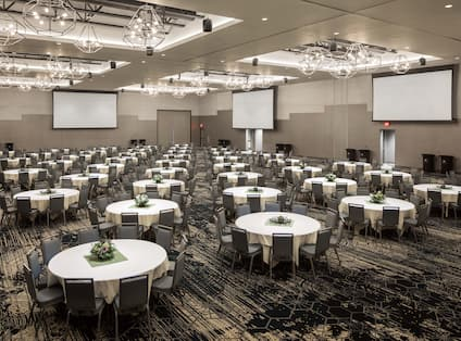 Large Ballroom with Round Tables and Three Projector Screens
