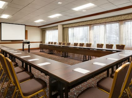 Meeting Room with U-Shaped Conference Table and Projector Screen