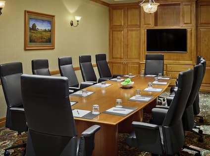 a boardroom table and a wall mounted tv in a meeting room