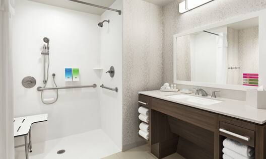 Spacious accessible bathroom featuring roll in shower with seat, mobile shower head, large vanity, and mirror.