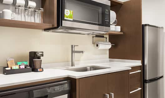 Fully equipped kitchen in studio suite featuring fridge, dishwasher, microwave, and coffee maker.