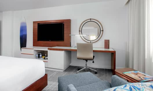 a bed, lounge chair, desk and tv in a guest room