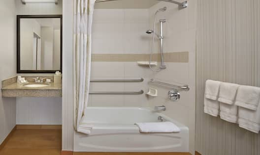 Vanity Mirror, Sink, Toiletries, and Accessible Bathtub With Handrails, Seat, Handheld Showerhead and Towels,