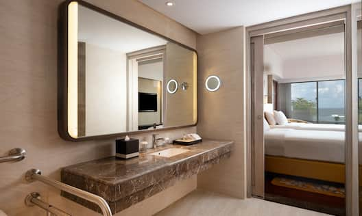 Accessible Room Vanity Area with Mirror and Partial View of Bedroom
