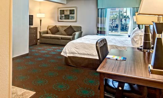View of Suite with Large Bed Desk and Living Area