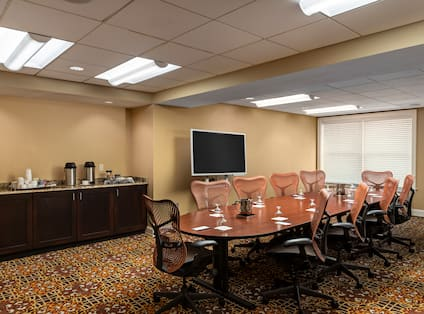 boardroom round table setup with large TV