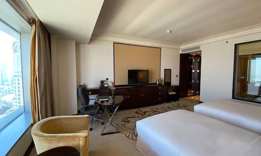 Guestroom with beds, work desk and TV