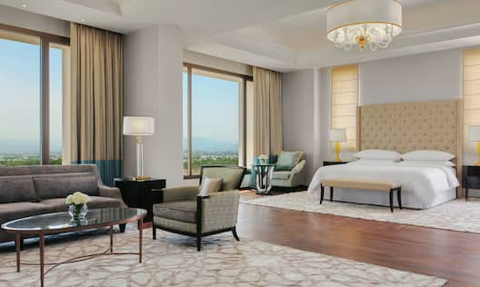 Bedroom Area of Presidential Suite with King Bed, Lounge Area and City Views