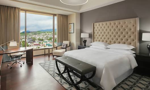 Bedroom Area of Suite with Kingbed, Twin Bedroom with Work Desk, City Views, and Seating Area