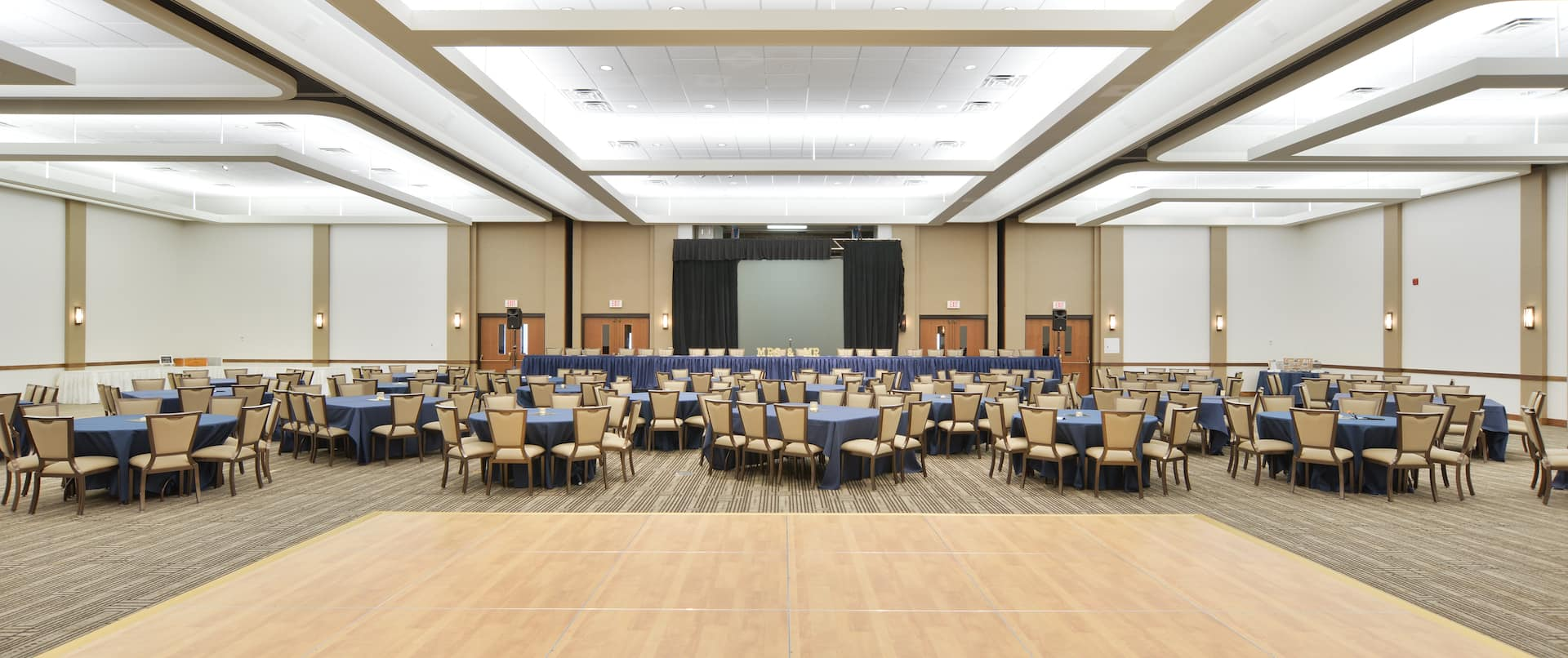 Dance Floor, Mixed Tables With Blue Linens, Tan Chairs, and Head Table In Front of Large Presentation Screen With Black Drapes Set Up in Large Banquet Space