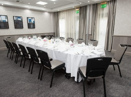 16 Place Settings on Long Table With White Linens for Private Dinner in Meeting Space With Wall Art and Windows With Long Drapes