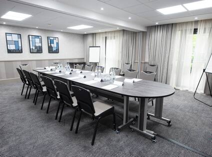 Boardroom With Seating for 14 Around Table, Wall Art, Two Presentation Easels, Two Speaker's Chairs and Window With Long Drapes