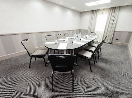 Meeting Room With Seating for Nine Around Boardroom Table With Water Bottles and Window With Long Drapes