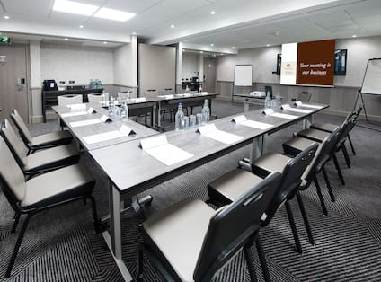 Meeting Room With Seating for 15  Around U-Table Facing Projector Table, Presentation Screen and Two Easels With Refreshment Areas along Side Wall