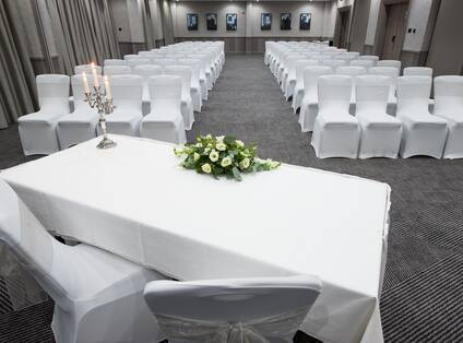 Front View of Meeting Room Arranged Theater Style With Rows of White Chairs Facing Table With Two Chairs, Candles and Flowers on White Linens