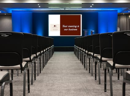 Meeting Room Arranged Theater Style With Rows of Black Chairs Facing Projector Screen and Podium