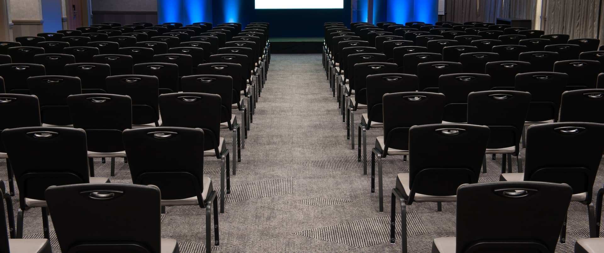Edinburgh Suite Arranged Theater Style With Rows of Black Chairs Facing Dramatically Lit Projector Screen and Podium