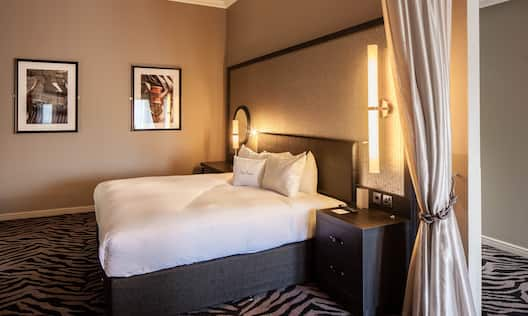 Wall Art, King Bed, Illuminated Lamps Above Bedside Tables With Connectivity Ports, and Partition Drape in Junior Suite