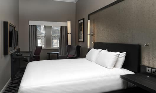 King Bed, Illuminated Lights Above Bedside Tables With Connectivity Ports, TV, Work Desk, Window With Open Drapes, Armchair and Wall Art in Deluxe Room with View