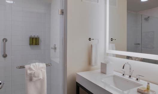 Bathroom Vanity Area with Lit Mirror and Glassdoor Shower