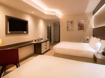 Wall Art, Two Queen Beds,  Bedside Tables With Reading Lamps, Work Desk, TV, Hospitality Center, Full Length Mirror and View Towards Entry in Deluxe Family