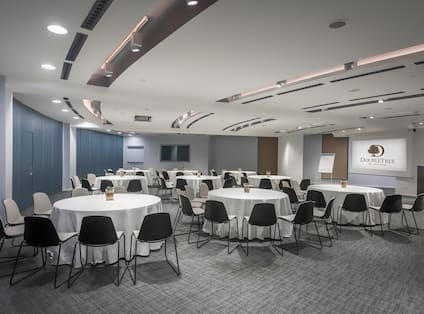 Cabaret Setup in Milano Meeting Room With Round Tables and Chairs Facing Easel, Presentation Screen, and Podium