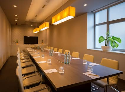 Chicago Meeting Room With Wall Clock, TV, and Seating for 20, Beverages and Notepads on Boardroom Table, and Window With Frosted Glass